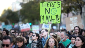 A young man carries a sign 'There's no planet B' while taking part in a World Climate March in Lisbon, Sunday, Nov. 29 2015. (AP / Armando Franca)