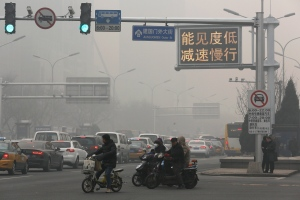 Motorists wait at a junction as vehicles pass beneath a traffic sign reading 'Visibility low, slowdown the speed' on a heavily polluted day in Beijing, Monday, Nov. 30, 2015. (AP/Andy Wong)