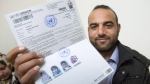 Mjdi Mnaahe shows off his UNHCR registration papers, Monday, November 30, 2015 in the Irbid, Jordan. The Syrian refugee and his family are waiting for approval to immigrate to Canada. THE CANADIAN PRESS/Paul Chiasson