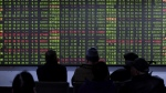 Chinese investors are silhouetted by an electronic information display as they monitor stock prices at a brokerage house in Hangzhou in eastern China's Zhejiang province on Friday, Nov. 27, 2015. (Chinatopix)