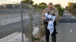 Deputy Adam Collette holding an infant girl where she was found abandoned under asphalt and rubble, near a bike path in Compton, Calif. on Friday, Nov. 27, 2015. (Los Angeles County Sheriff's Department)