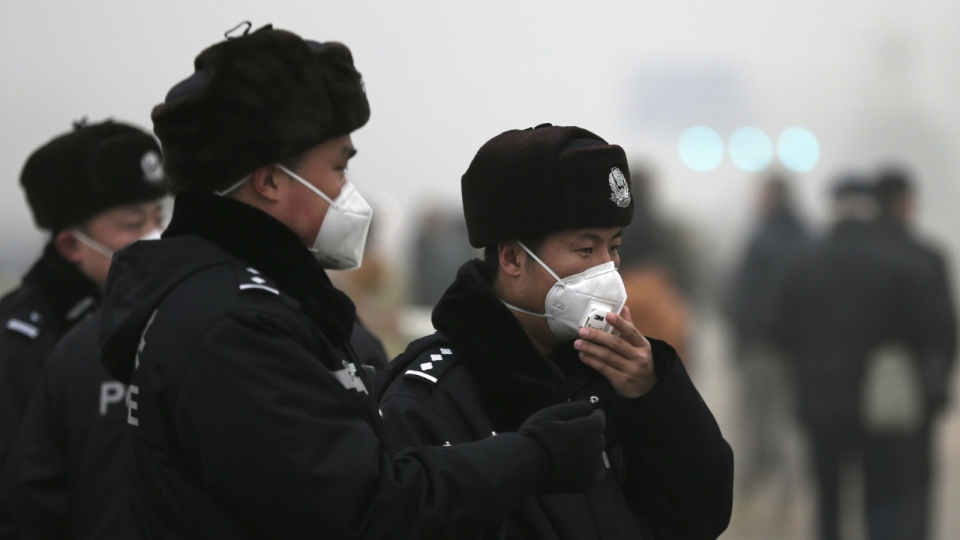 A policeman adjusts his mask as he and his colleagues perform their duty near Tiananmen Gate on a heavily polluted day in Beijing, Tuesday, Dec. 1, 2015. (AP / Andy Wong)