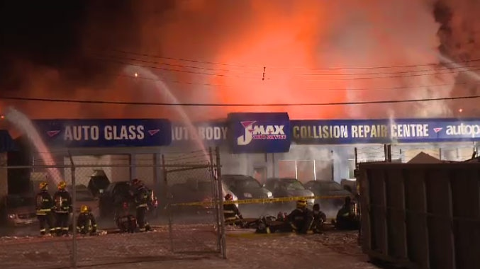 Firefighters battle a massive blaze at J Max Auto Service on Pembina Highway early Tuesday morning.