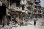 In this June 5, 2014, file photo, a man rides a bicycle through a devastated part of Homs, Syria. (AP/Dusan Vranic, File)