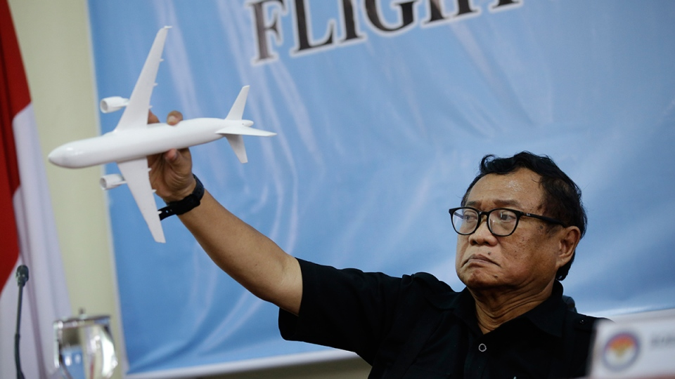 Indonesian National Transportation Safety Committee Chief Investigator Marjono Siswosuwarno uses a model plane to show the movement of AirAsia Flight QZ8501 before crashing into the Java Sea on Dec. 28, 2014, during a news conference in Jakarta, Indonesia, Tuesday, Dec. 1, 2015. (AP / Achmad Ibrahim)