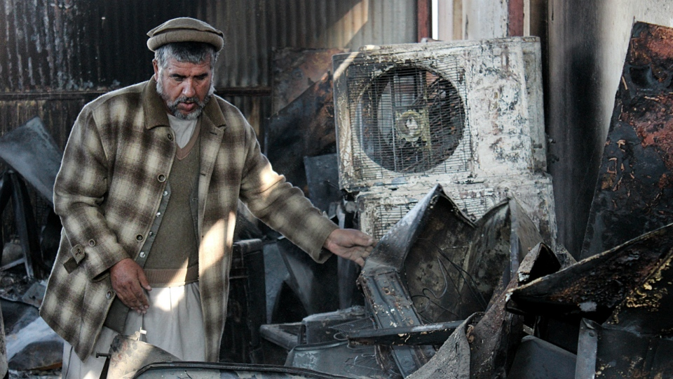 An Afghan business man salvages what he can from his warehouse that was destroyed from fighting in Kunduz city, north of Kabul, Afghanistan on Tuesday, Dec. 1, 2015. (AP / Najim Rahim)