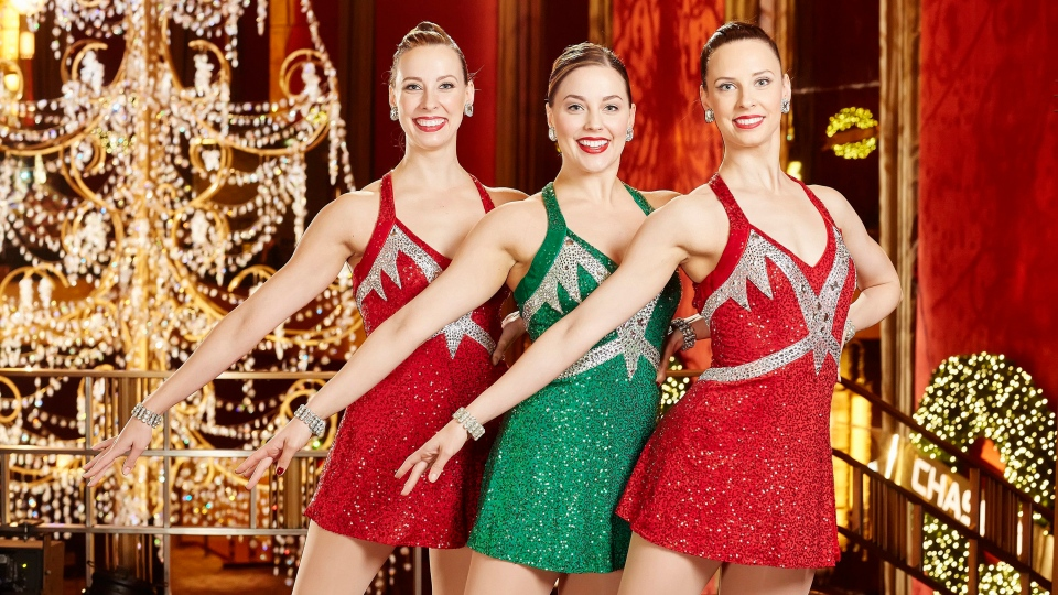 Radio City Rockettes, Kristin, from left, Alison and Lisa Jantzie, are seen posing on the mezzanine at Radio City Music Hall during the 2015 Radio City Christmas Spectacular in New York. (Carl Scheffel/MSG via AP)