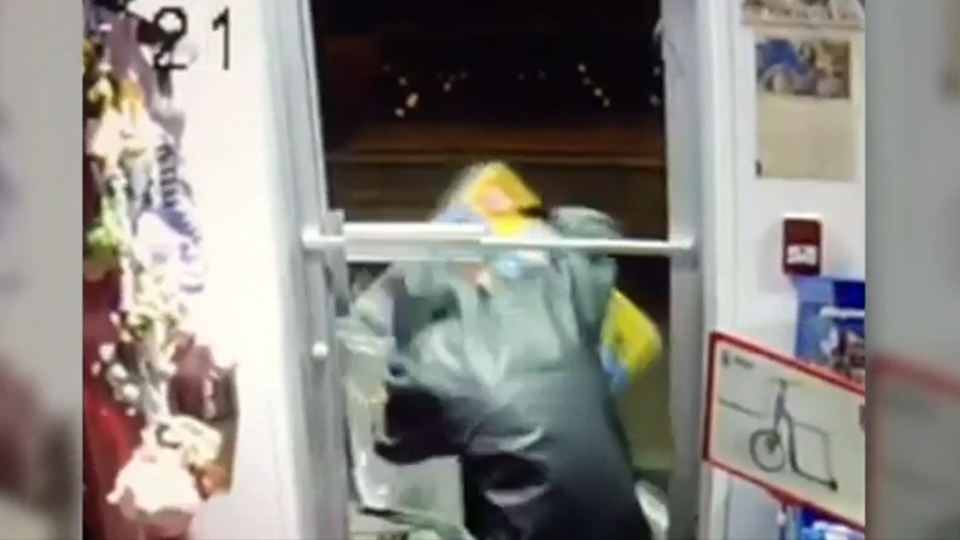 A suspect is seen leaving through the shattered door of the Granville Island Toy Company with a stolen Lego set in hand.