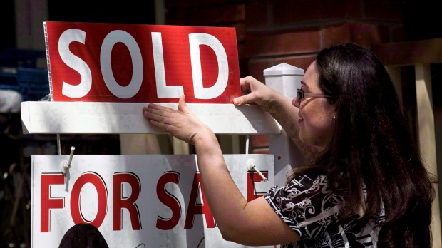 A woman places a 'sold' sign in front of a home in this file photo. (Darren Calabrese / The Canadian Press)