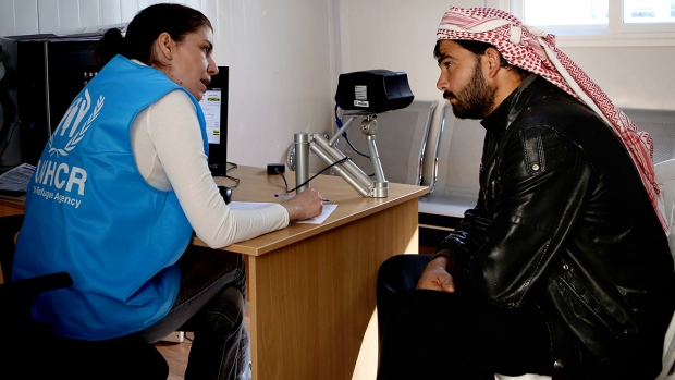 A Syrian refugee man listens to an employee