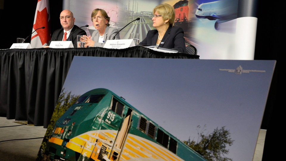 The train damaged in the 2013 collision between a Via Rail train and OC Transpo bus is seen as Transportation Safety Board Investigator-in-charge Rob Johnston (left), TSB Chair Kathy Fox and Board Member Helene Gosselin speak to media after releasing the final report in Ottawa on Wednesday, Dec. 2, 2015. (Justin Tang / THE CANADIAN PRESS)