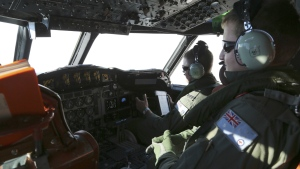 Flight engineer Sgt. Jush Rumis, right, keeps a look out while on board a Royal Australian Air Force AP-3C Orion, during a search for the missing Malaysia Airlines flight MH370 in southern Indian Ocean off the coast of Western Australia on March 22, 2014. (AP / Rob Griffith)