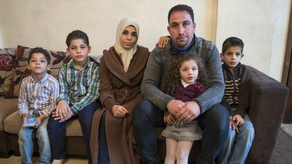 Syrian refugee Awad Alhajali from Kherbet Ghazalah, Syria and his wife Asmaa sit with their children, Obaida, 5, Adnan, 9, Abedr, 2, and Obada, 7, left to right, in their apartment in Irbid, Jordan on Monday, Nov. 30, 2015. (Paul Chiasson / THE CANADIAN PRESS)