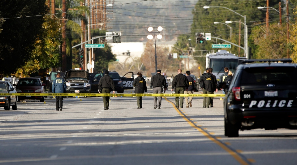 Investigators search for bullet casings at the scene where Wednesday's police shootout with suspects took place in San Bernardino, Calif., Thursday, Dec. 3, 2015. (AP / Jae C. Hong)