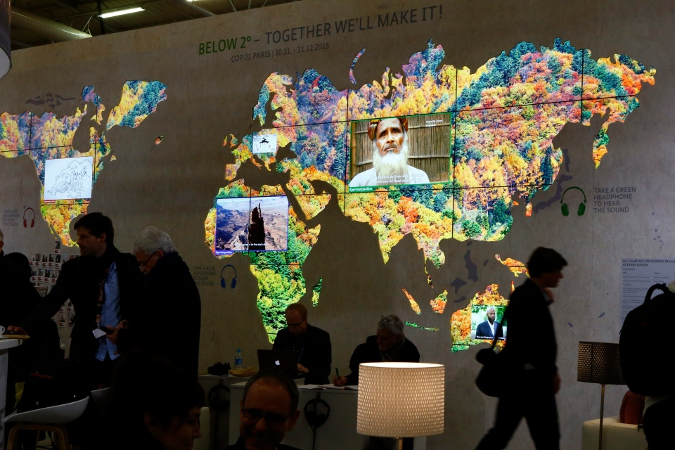 People pass a world map at the German pavillon entitled 'Below 2 degrees, Together we'll make it' during the COP21, United Nations Climate Change Conference, in Le Bourget, north of Paris, Thursday, Dec. 3, 2015. (AP / Francois Mori)