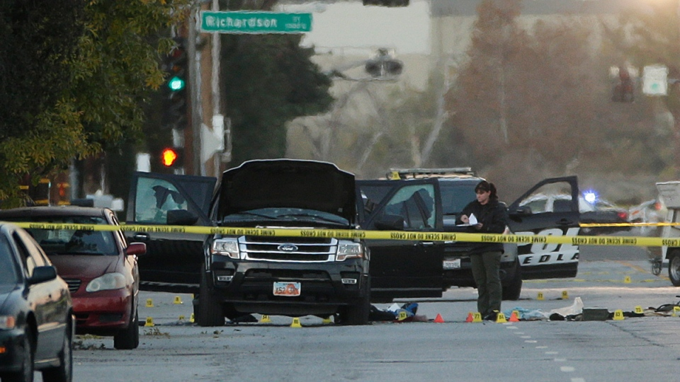 An investigator looks at a Black SUV that was involved in a police shootout with suspects, in San Bernardino, Calif., Thursday, Dec. 3, 2015. (AP / Jae C. Hong)