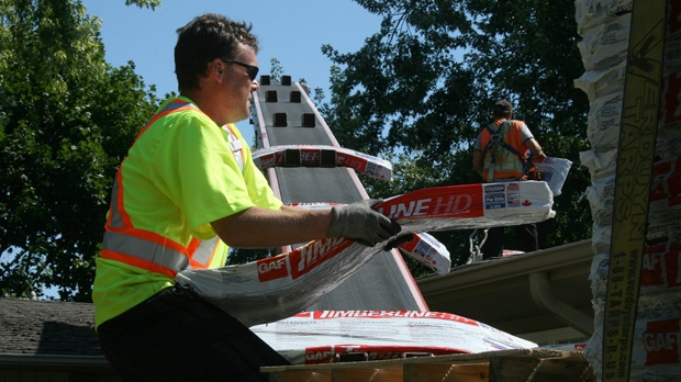 A worker unloads packages of shingles from a truck for a roofing job on a house in Oakville, Ont., July 31, 2015. THE CANADIAN PRESS IMAGES/Richard Buchan