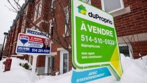For sale signs are seen in front of a Montreal condominium, Tuesday, March 17, 2015. (THE CANADIAN PRESS/Paul Chiasson)