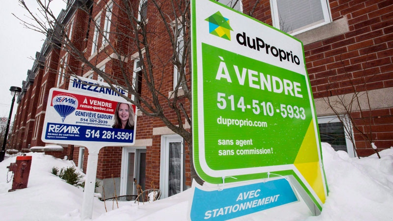 For sale signs are seen in front of a Montreal condominium on Tuesday, March 17, 2015. (Paul Chiasson / THE CANADIAN PRESS)