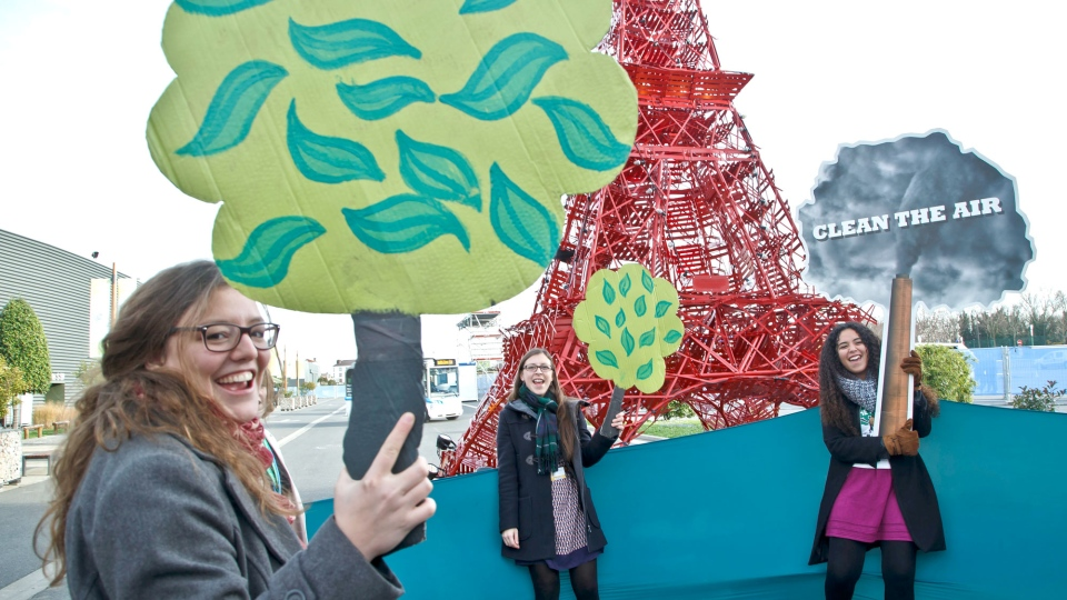 "Representatives of NGOs hold cut out of trees and shout""clean the air, plant a tree"", in front of a reproduction of the Eiffel tower at the COP21, United Nations Climate Change Conference, in Le Bourget north of Paris, Saturday, Dec. 5, 2015. (AP / Michel Euler)"