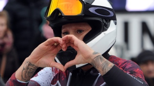 Kaillie Humphries of Canada makes a heart shape with her hands as she celebrates the third place during the women's competition of the two-man bobsled World Cup in Winterberg, Germany on Dec, 5, 2015. (Caroline Seidel / dpa via AP)