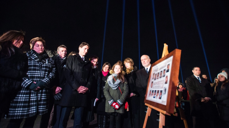 Beams of light, one for each victim, shine over Prime Minister Justin Trudeau as he takes part in a memorial ceremony for the fourteen women murdered at Ecole Polytechnique on December 6, 1989, twenty six years ago today, Sunday, Dec. 6, 2015. (Paul Chiasson / THE CANADIAN PRESS)