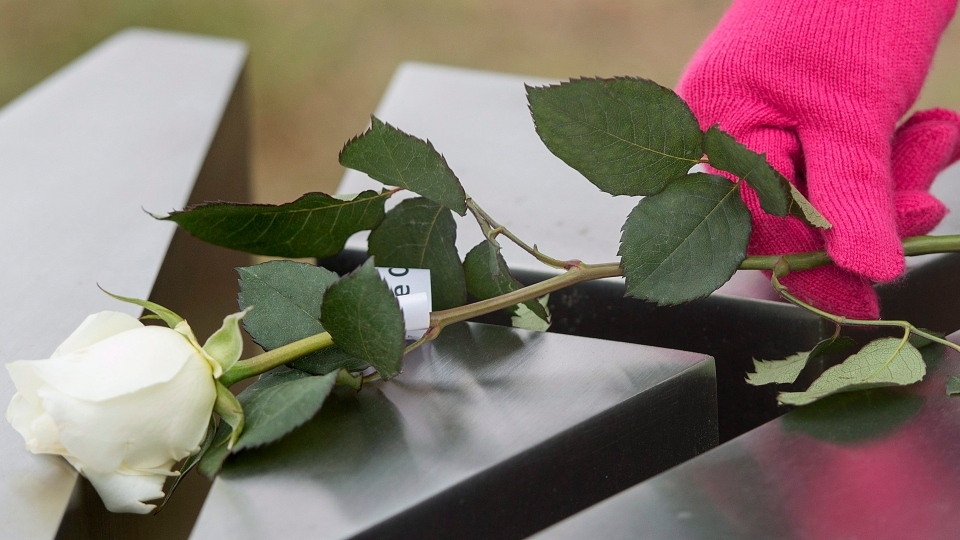 A woman places a rose on a memorial of one of the 14 women murdered a Ecole Polytechnique on December 6, 1989, during a ceremony to mark the 26th anniversay of the massacre, in Montreal, on Dec. 6, 2015. (Graham Hughes / The Canadian Press)