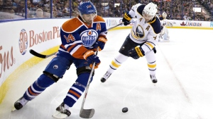 Buffalo Sabres' Josh Gorges and Edmonton Oilers' Jordan Eberle battle for the puck during second period NHL action in Edmonton, Alta., on Sunday, Dec. 6, 2015. (Jason Franson / THE CANADIAN PRESS)