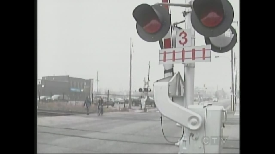 Pedestrians cross train tracks where a cyclist was struck by a train on the weekend in London, Ont. on Monday, Dec. 7, 2015. (Sean Irvine / CTV London)