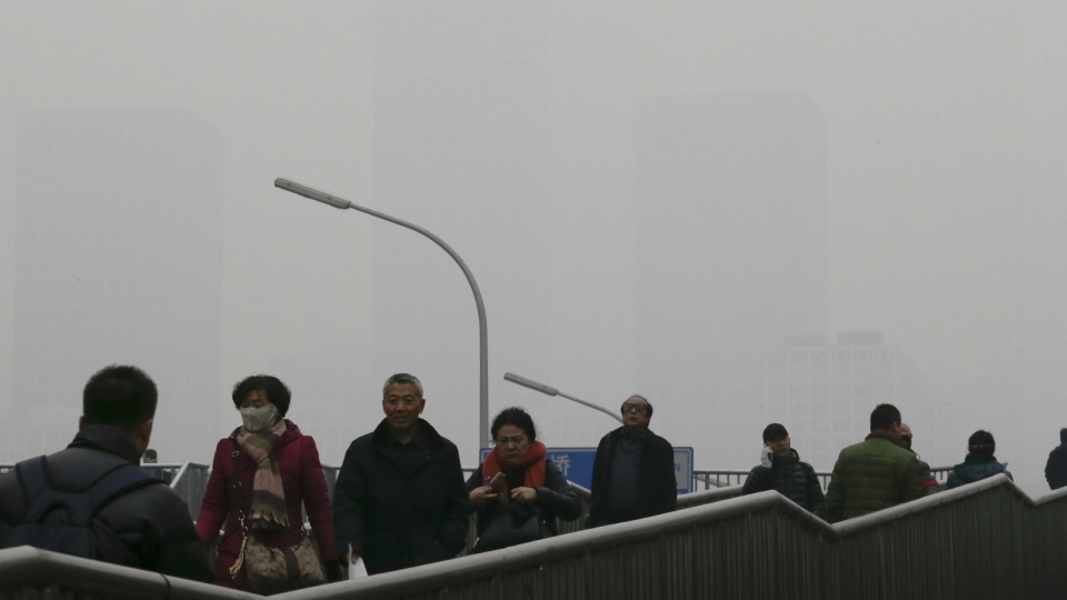 People walk on a pedestrian overhead bridge as office buildings in Central Business District of Beijing are shrouded with heavy haze, Tuesday, Dec. 8, 2015. (AP / Andy Wong)