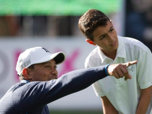 Tiger Woods gives pointers as he works with a young golfer, during a promotional clinic as part of the Bridgestone America's Golf Cup in Mexico City, Tuesday, Oct. 20, 2015. (AP/Rebecca Blackwell)