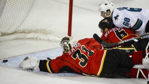 San Jose Sharks' Melker Karlsson, right, dives for the puck with Calgary Flames' Dennis Wideman, centre, and goalie Karri Ramo, during second period NHL hockey action, in Calgary, on Tuesday, Dec. 8, 2015. (Jeff McIntosh / THE CANADIAN PRESS)