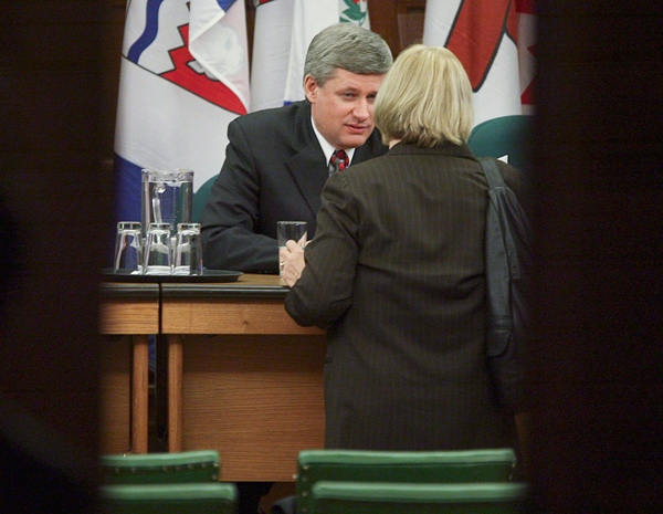 Prime Minister Stephen Harper speaks with a caucus member following meetings on Parliament Hill in Ottawa, Wednesday, Dec. 10, 2008. (Sean Kilpatrick / THE CANADIAN PRESS)