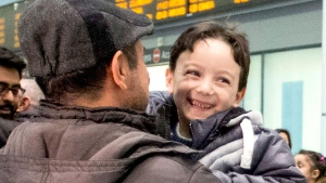 Six-year-old Ahmad Mazan Khabbaz smiles as he is greeted by family friend Rakan Almasri, himself a recent arrival to Canada from Syria, as the youngest member of his family arrives with his parents and sisters at Toronto's Pearson Airport, on Wednesday, Dec. 9, 2015.  (THE CANADIAN PRESS/Chris Young)