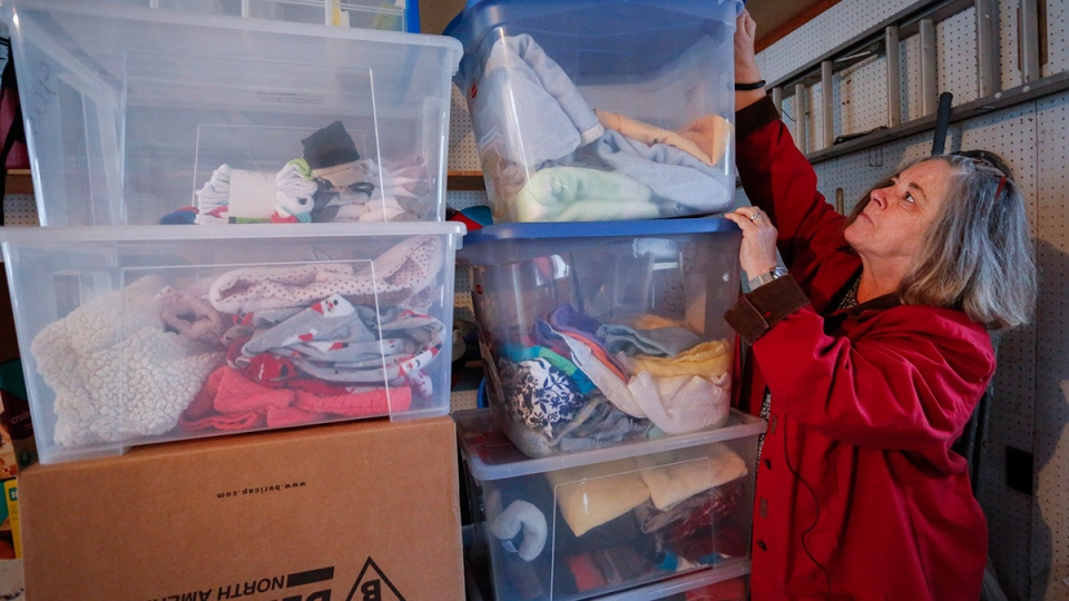 Karen Huggins sorts through donated items for Syrian refugee children in her garage in Calgary, Tuesday, Dec. 8, 2015. (Jeff McIntosh / THE CANADIAN PRESS)