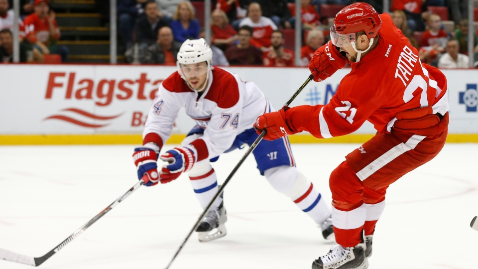 Detroit Red Wings left wing Tomas Tatar (21) shoots as Montreal Canadiens  defenseman Alexei Emelin (74) defends in the second period of an NHL hockey  game ... 160fe6542