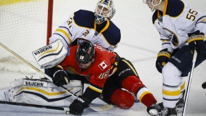 Buffalo Sabres' Rasmus Ristolainen, right, checks Calgary Flames' David Jones, centre, into goalie Chad Johnson during third period NHL hockey action, in Calgary, on Thursday, Dec. 10, 2015. (Jeff McIntosh / THE CANADIAN PRESS)