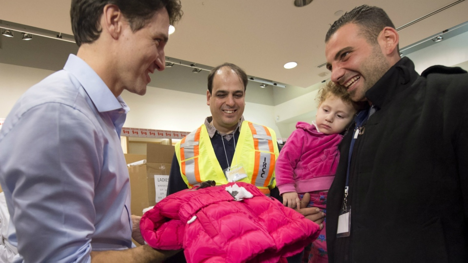 Prime Minister Justin Trudeau greets refugees from Syria with cold-weather clothing as they arrive at Pearson International airport, in Toronto, on Friday, Dec. 11, 2015. (Nathan Denette / THE CANADIAN PRESS)