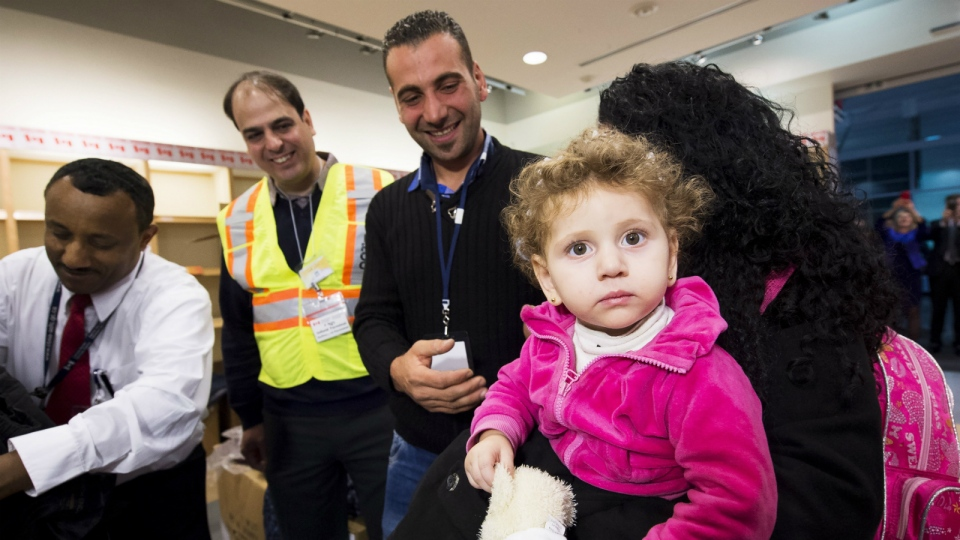 Sixteen-month-old Madeleine Jamkossian, right, arrives with her family, refugees fleeing the Syrian civil war, at Pearson International airport, in Toronto, on Friday, Dec. 11, 2015. (Nathan Denette / THE CANADIAN PRESS)