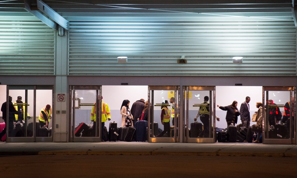 Workers help newly arrived Syrian refugees load their luggage onto buses at Pearson International airport, in Toronto, on Friday, Dec. 11, 2015. (Nathan Denette / THE CANADIAN PRESS)