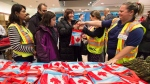 Newly-arrived Syrian refugee Anjilik Jaghlassian, centre, and her family receive winter clothes and other items at Pearson International airport, in Toronto, on Friday, Dec. 11, 2015. (THE CANADIAN PRESS / Nathan Denette)