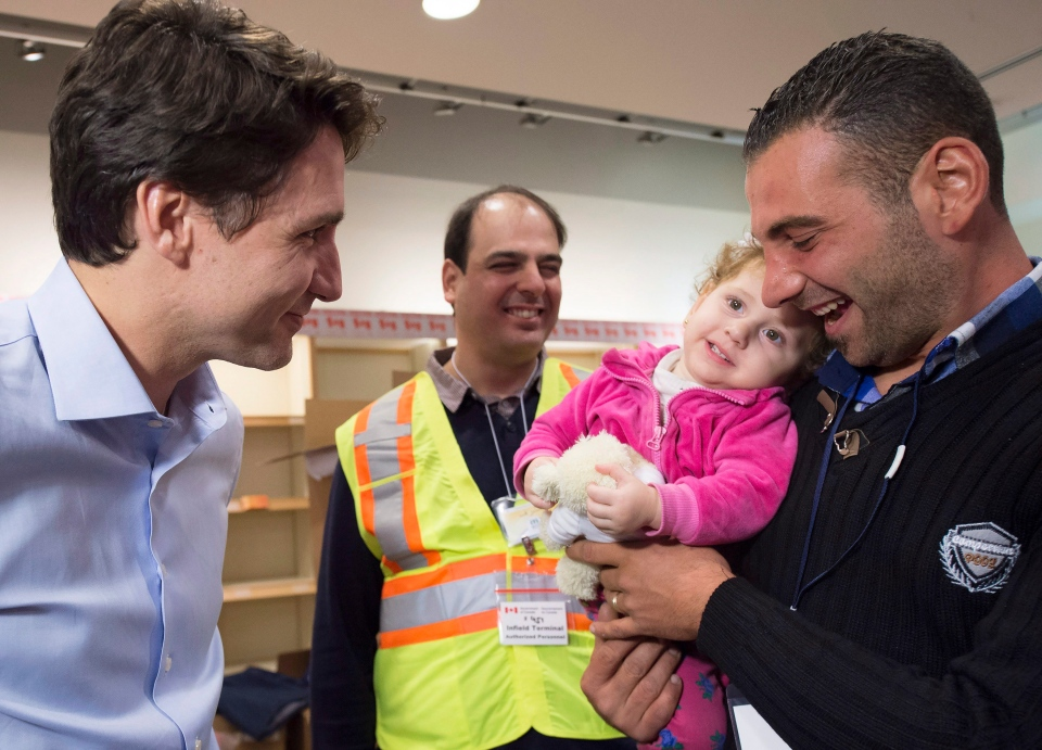 Canadian Prime Minister Justin Trudeau, left, receives a thank you from newly-arrived 16 month-old Madeleine Jamkossian, right, and her father Kevork Jamkossian, refugees fleeing the Syrian civil war, at Pearson International airport, in Toronto, on Friday, Dec. 11, 2015. (THE CANADIAN PRESS/Nathan Denette)