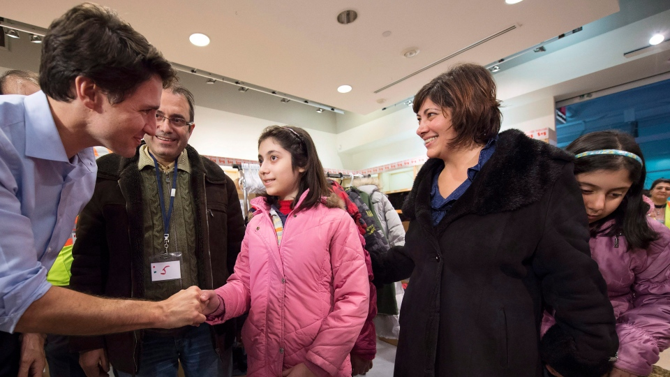 Prime Minister Justin Trudeau greets newly-arrived Syrian refugees Lucie Garabedian, centre, her father Vanig Garabedian, second left, mother Anjilik Jaghlassian, second right, and sister Anna-Maria Garabedian, right, at Pearson International airport, in Toronto, on Friday, Dec. 11, 2015. (Nathan Denette/The Canadian Press)