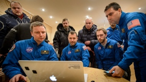In this photo provided by NASA, members of NASA and the Russian support teams watch a live video stream of the U.S. space agency's Kjell Lindgren, Russia's Oleg Kononenko and Kimiya Yui of Japan returning to Earth. (NASA/Bill Ingalls)