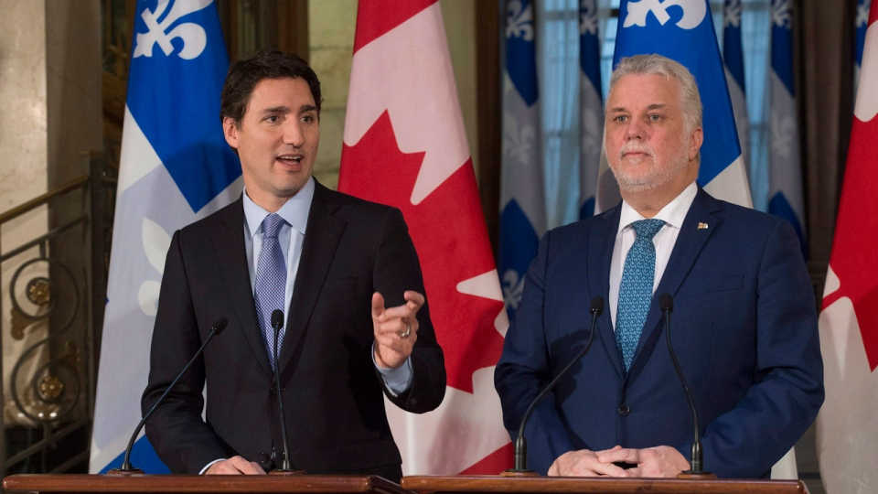 Prime Minister Justin Trudeau responds to reporters' questions at a news conference, while Quebec Premier Philippe Couillard, right, looks on at the Premier's Quebec City office, on Friday, Dec. 11, 2015. THE CANADIAN PRESS/Jacques Boissinot