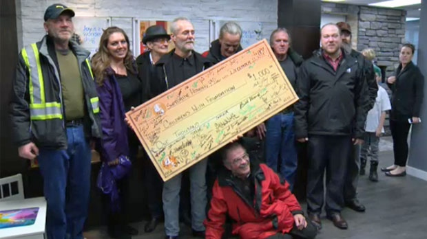 Drop-In Centre residents present the Children's Wish Foundation with a cheque for $1,000 on December 11, 2015