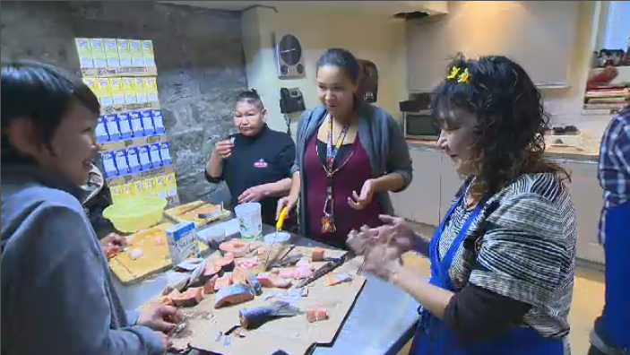 Clients and staff at Chez Doris, a women's day shelter in Montreal, prepare a lunch featuring traditional Inuit dishes. The centre is holding an open house fundraiser this weekend.