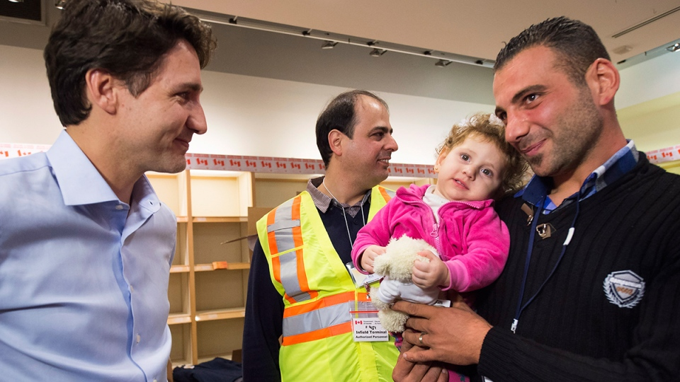 Prime Minister Justin Trudeau, left, receives a thank you from newly-arrived 16 month-old Madeleine Jamkossian, right, and her father Kevork Jamkossian, refugees fleeing the Syrian civil war, at Pearson International airport, in Toronto, on Friday, Dec. 11, 2015. (Nathan Denette / THE CANADIAN PRESS)