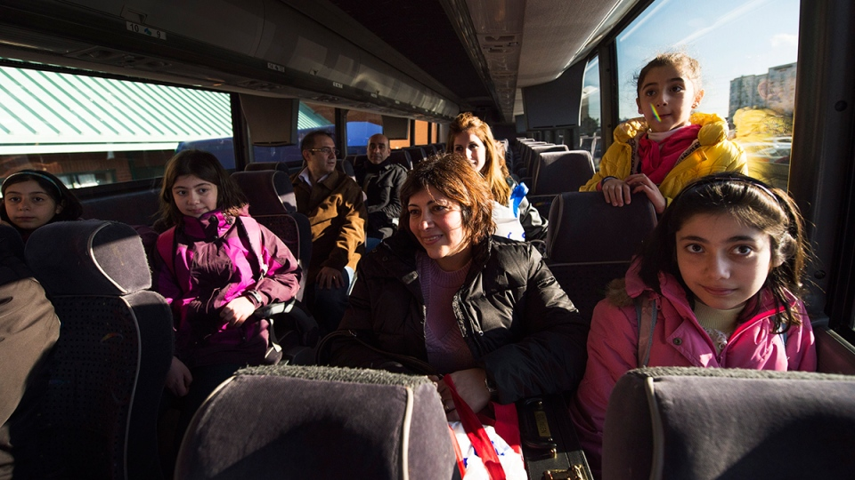Syrian refugees Lucie Garabedian, right, mother Anjilik Jaghlassian, centre, Sylvie Garabedian, second left, and younger sister Anna-Maria Garabedian, left, wait on the bus to depart for the Armenian Community Centre, in Toronto, on Friday, Dec. 11, 2015. (Nathan Denette / THE CANADIAN PRESS)