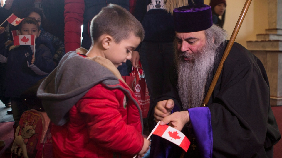 Syrian Refugee, four year-old Levon Kourken, left, is greeted by Armenian Orthodox Priest Meghrig Parikian as he arrives at the St. Mary Armenian Apostolic Church, where Syrian refugees arrived this morning, in Toronto, on Friday, Dec. 11, 2015. (Chris Young / THE CANADIAN PRESS)